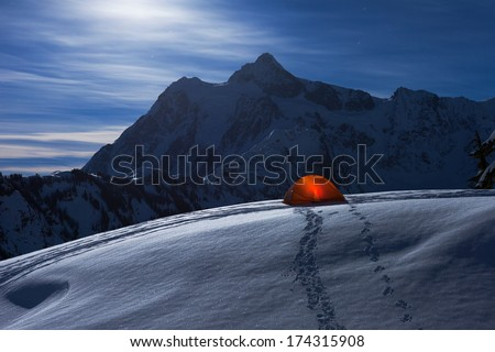 Glowing Tent under Moonlight on Snow Mountain - stock photo