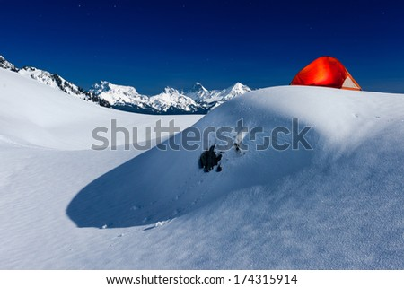 Glowing Tent under Moonlight on Snow Mountain - stock photo