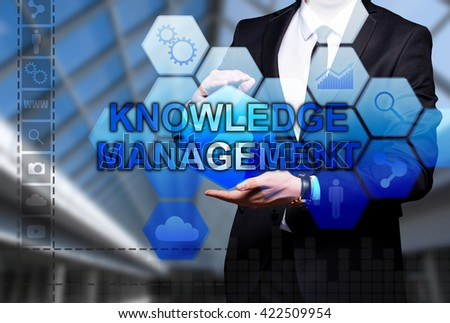 "Glowing text ""Knowledge Management"" in the hands of a businessman. Business concept. Internet concept."