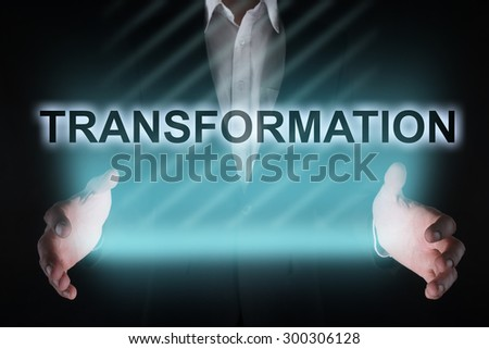 "Glowing text ""transformation"" in the hands of a businessman. Business concept - stock photo"