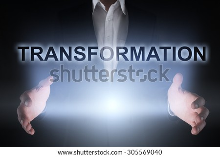 """Glowing text """"transformation"""" in the hands of a businessman. Business concept. - stock photo"""
