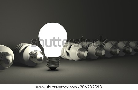 Glowing tungsten light bulb standing in row of lying switched off fluorescent ones on gray textured background