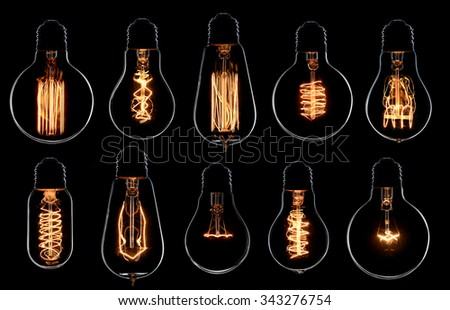 Glowing vintage light bulbs set. Black background - stock photo