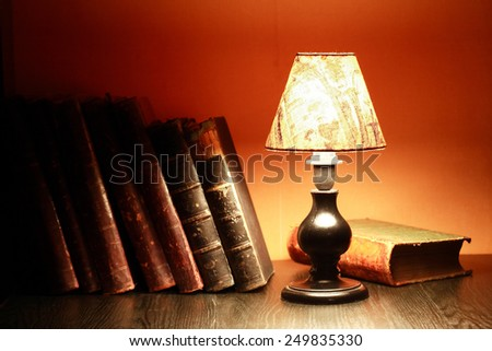 Glowing vintage table lamp near stack of old books - stock photo