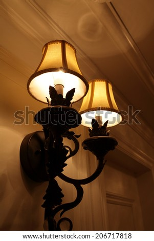 Glowing wall lamp in the hotel at night - stock photo