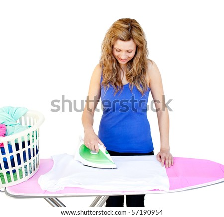 Glowing woman ironing her clothes on a ironing board against white background