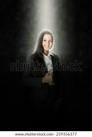 Glowing Young Businesswoman Showing Thumbs up Hand Sign with a Smile on an Abstract Black Background.