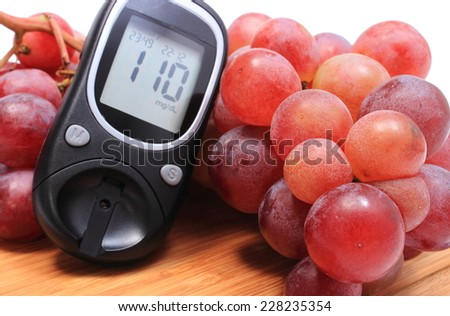 Glucometer and fresh natural bunch of grapes on wooden cutting board, concept for healthy eating and diabetes - stock photo