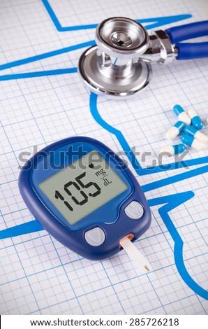 Glucometer and stethoscope on medical background - stock photo