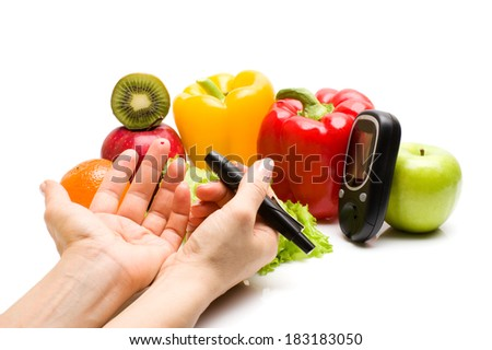 glucometer for glucose level blood test in hand and healthy organic food on a white background. Diabetes concept - stock photo