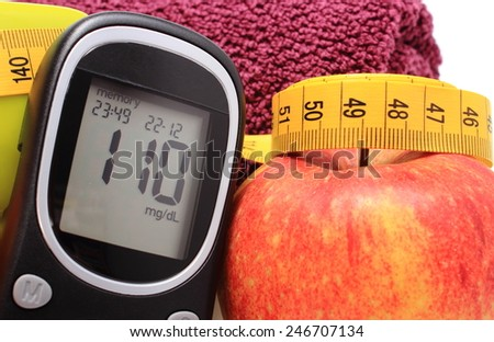 Glucometer, fresh apple and tape measure, concept for diabetes, lifestyle and healthy nutrition - stock photo