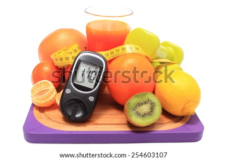 Glucometer. fresh fruits, dumbbells for using in fitness, tape measure and glass of juice, concept for diabetes, slimming, healthy nutrition and strengthening immunity