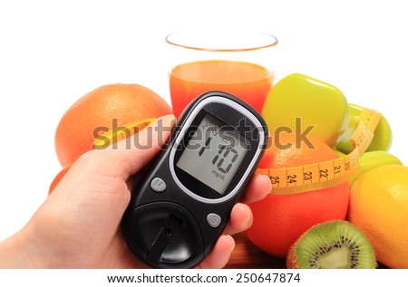 Glucometer in hand. fresh fruits, dumbbells for using in fitness, tape measure and glass of juice, concept for diabetes, slimming, healthy nutrition and strengthening immunity - stock photo