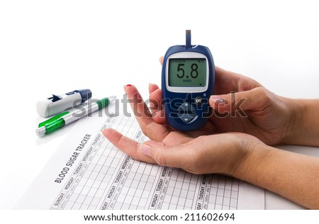 glucometer in woman's  hand, display of glucometer showing  number 5.8, on white background with medical form and pen