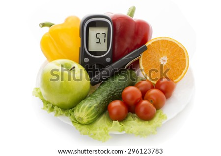 glucometer with figures 5.7 and healthy organic food on a white background