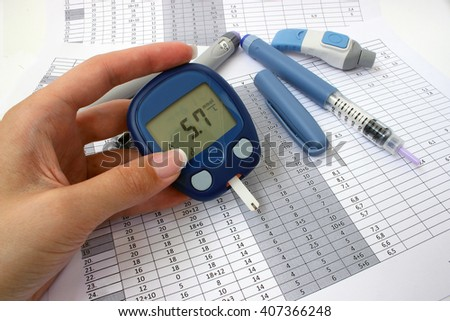 Glucometer with normal blood glucose levels in a female hand