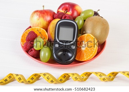 Glucose meter for measuring and checking sugar level, fruits on plate and tape measure, concept of diabetes, slimming and healthy nutrition