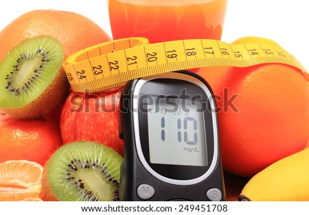 Glucose meter, fresh ripe natural fruits with tape measure and glass of juice on cutting board, concept for diabetes, healthy nutrition and strengthening immunity - stock photo