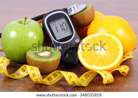 Glucose meter with medical stethoscope, fresh ripe fruits and tape measure, orange kiwi apple, concept of diabetes and healthy lifestyles - stock photo