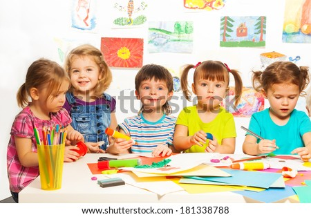 Gluing and painting lesson happy kids by the table - stock photo