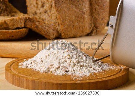 Gluten free flour with cutted fresh bred and breadmaker on wooden table - stock photo