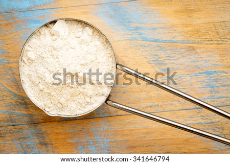 gluten free quinoa flour in a metal measuring cup  against painted wood - stock photo