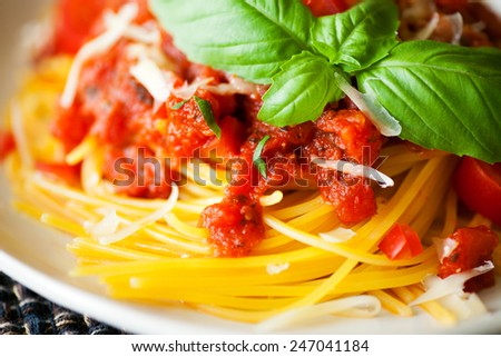 Gluten free spaghetti and tomato sauce with fresh basil and grated parmesan cheese. The pasta is made with Quinoa and corn flours.  - stock photo