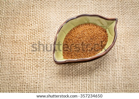 gluten free teff grain on a leaf shaped bowl against burlap canvas - stock photo
