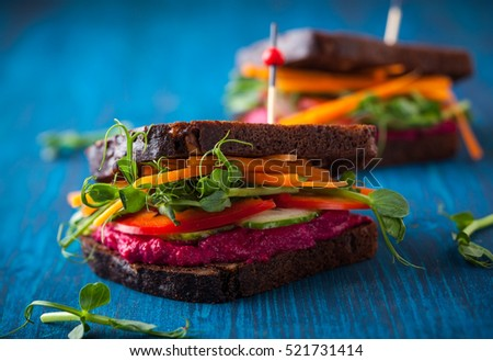 gluten free vegan sandwiches with beet hummus, raw vegetables and sprouts.