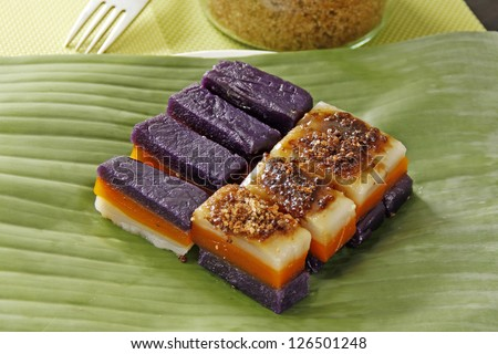Glutinous rice cake with different flavor per layer on banana leaf - stock photo