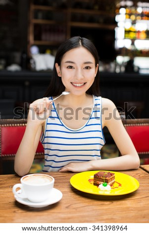 glutton girl sitting in cafe shop with hot beverage, delicious gourmet sweet cream cake . - stock photo