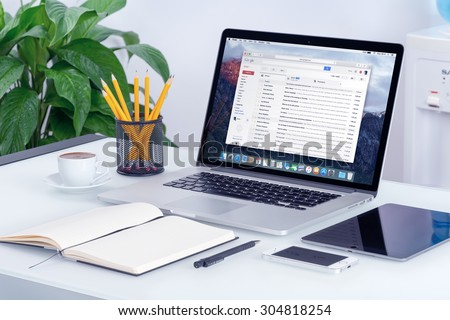 Gmail app on the iPhone display in man hands and Gmail desktop version on the Macbook screen. Gmail is a free email service provided by Google. Varna, Bulgaria - May 29, 2015. - stock photo