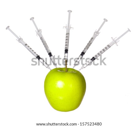 GMO food concept. Genetically modified green apple and syringes isolated on white background. Genetic injections - stock photo