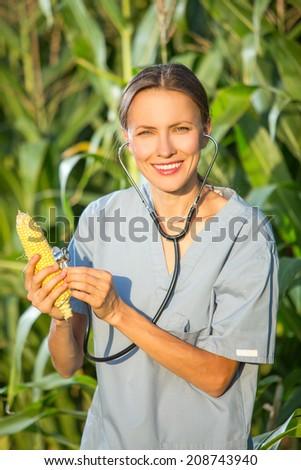 GMO,professional in uniform examining corn cob on field. Healthy organic food concept - stock photo