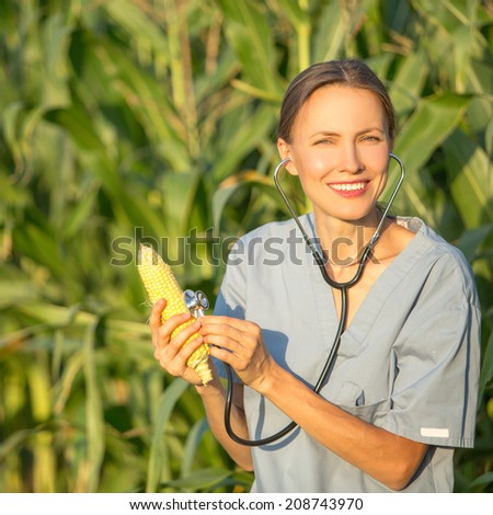 GMO,professional in uniform examining corn cob on field. Healthy organic food concept - stock photo