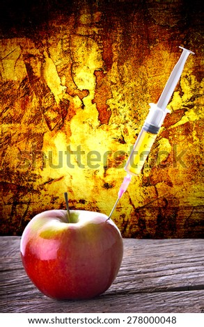 GMO syringe Injection into red apple dramatic abstract background - stock photo