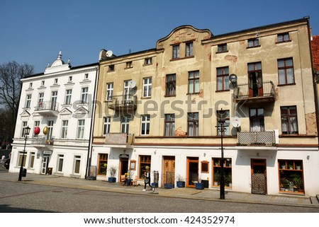 GNIEZNO, POLAND - APRIL 5, 2016. Residential building dating from 1914 on Tumska street in Gniezno, Poland with commercial shops and restaurants on the first floor, with people.