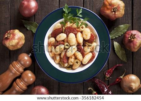 Gnocchi di patata, italian potato noodles with tomato sauce, olives and sausage - stock photo