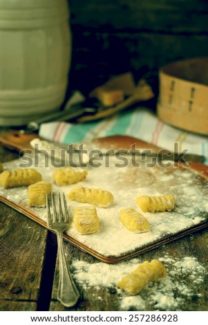 gnocchi , flour and parmigano on the wooden background.image is tinted  - stock photo