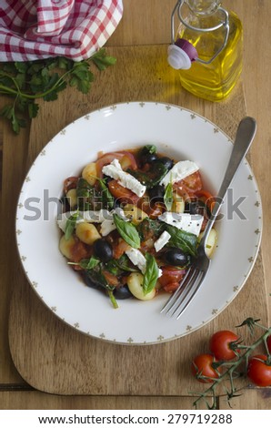 Gnocchi with feta, black olives and tomatoes topped with basil - stock photo