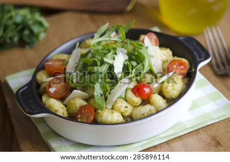 Gnocchi with pesto and rocket topped with shaved Parmesan - stock photo