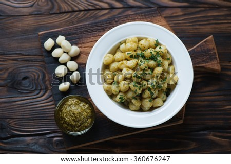 Gnocchi with pesto sauce on a rustic wooden background, top view