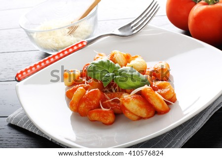 Gnocchi with tomato sauce and basil on complex background - stock photo
