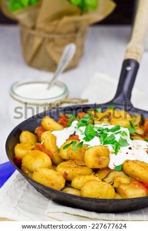 Gnocchi with zucchini, tomatoes and feta dip, selective focus - stock photo