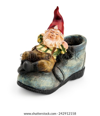 Gnome sitting on a boot isolated with clipping path  - stock photo