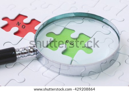 GO and NO puzzle with magnifier glass - stock photo