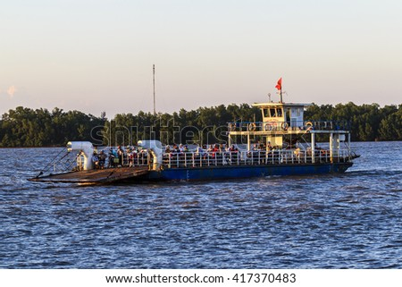 GO CONG, VIETNAM - MAY 07, 2016 - Tourists and cars loaded on a ferry and headed for the Go Cong Isle, Tien Giang province, Vietnam
