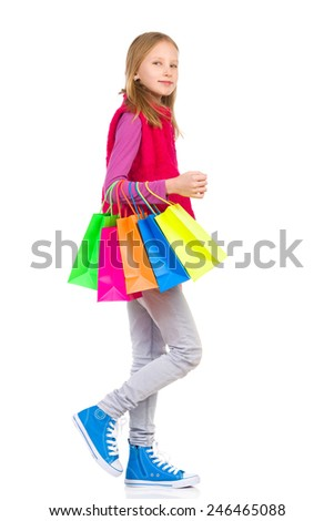 Go for a shopping. Young girl walking with colorful shopping bags. Full length studio shot isolated on white. - stock photo