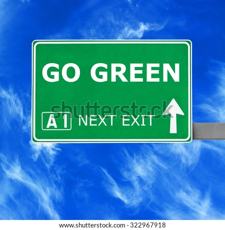 GO GREEN road sign against clear blue sky - stock photo