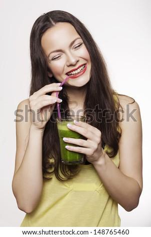 Go green. Young beautiful woman enjoying a healthy raw fruit vegetable juice. Studio shot. - stock photo